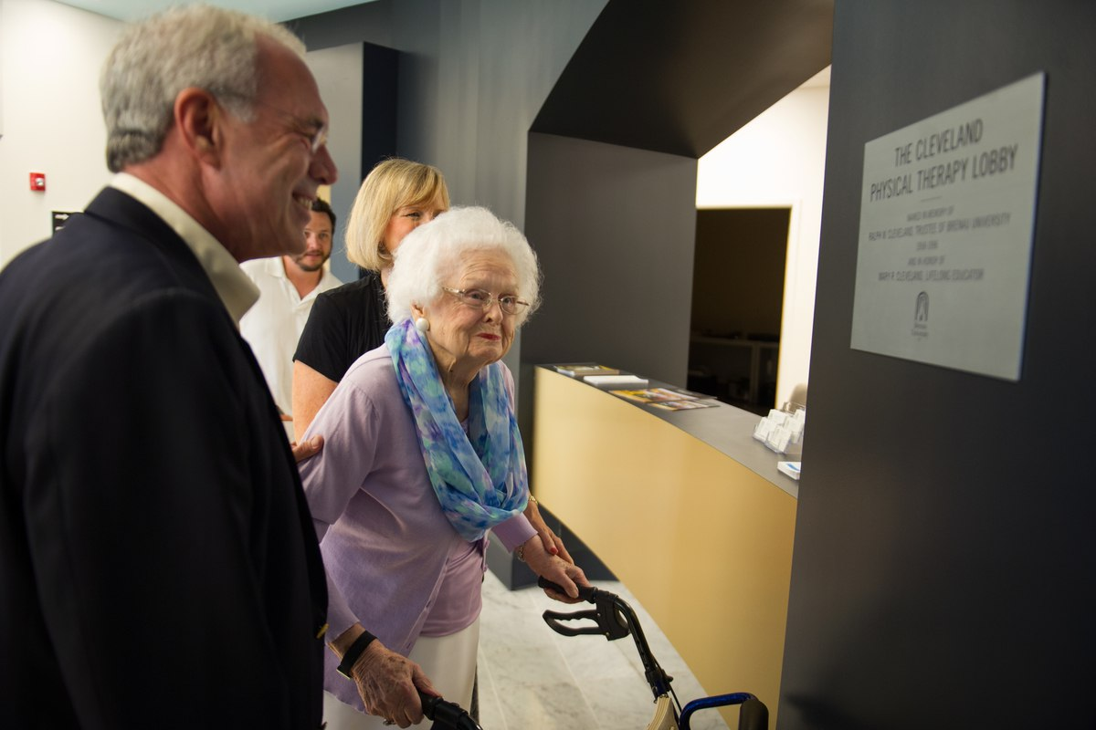 John R. Cleveland, left, shows his mother Mary Cleveland a plaque honoring her and her late husband Ralph Cleveland during the celebration to honor the dedication of The Cleveland Physical Therapy Lobby at the Brenau Downtown Center on Friday, July 3, 2015, in Gainesville, Ga. (AJ Reynolds for Brenau University)