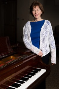 Karen Kulp poses for a photo with one of Brenau's Steinway Pianos (AJ Reynolds/Brenau University)